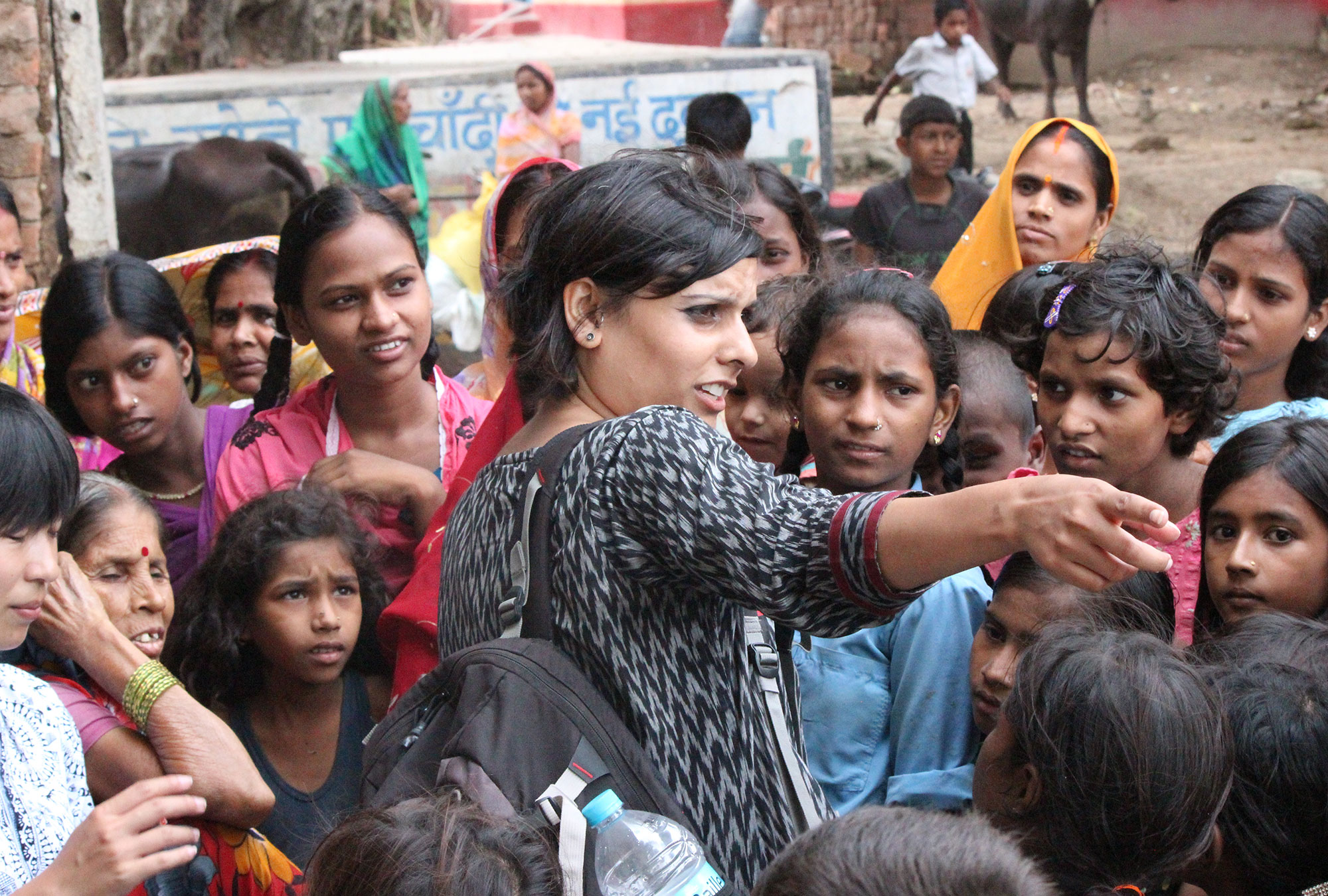 Dr. Sharma pointing in a crowd of children in India