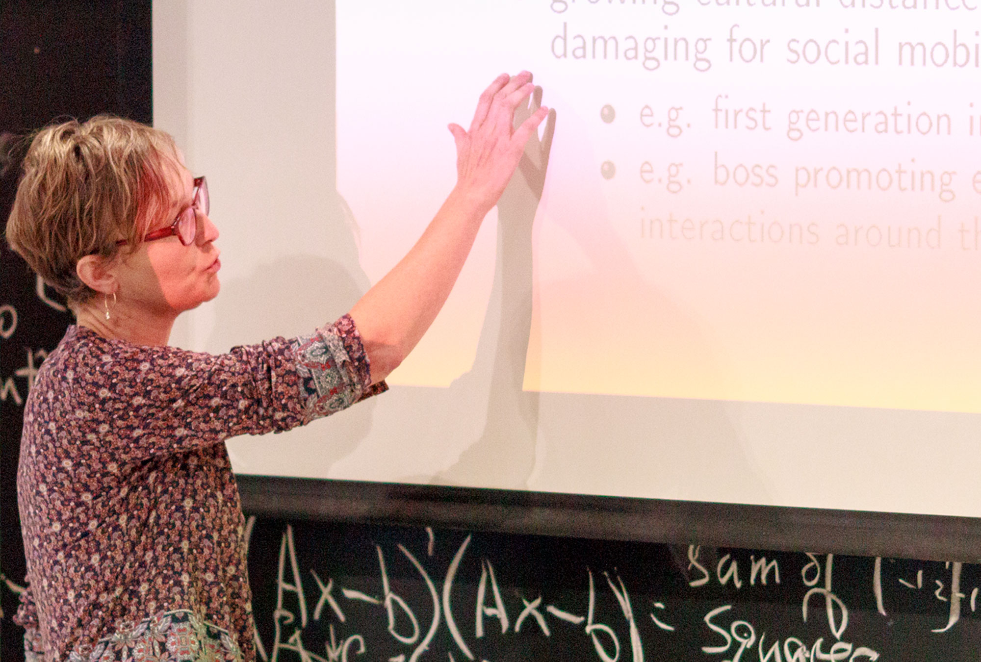 Marianne Bertrand lectures in front of a projector screen