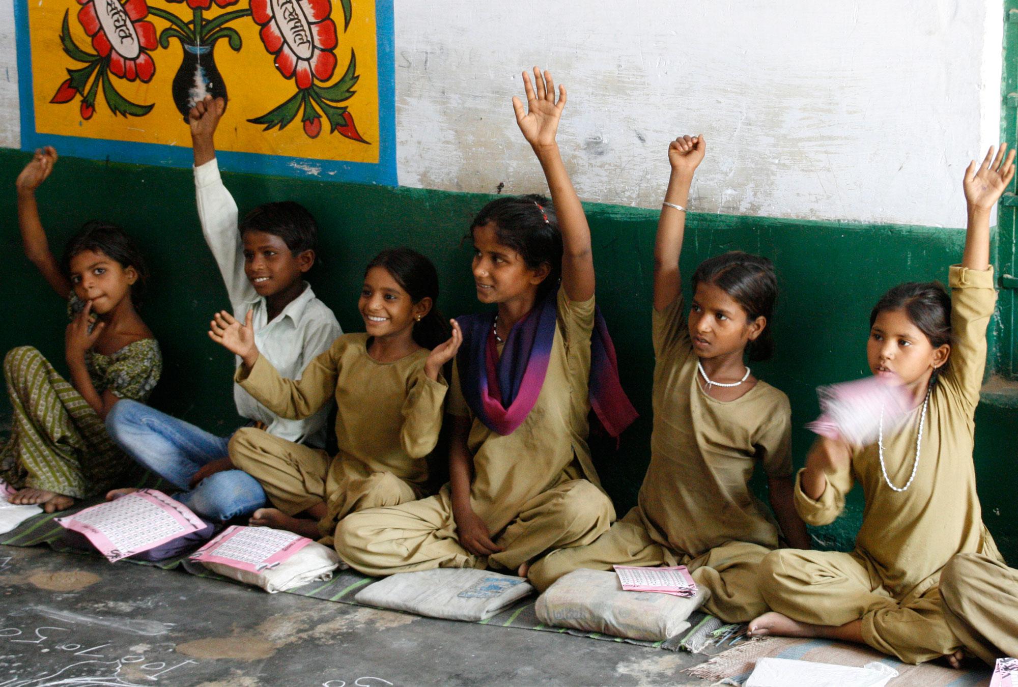 Schoolchildren in India raise their hands