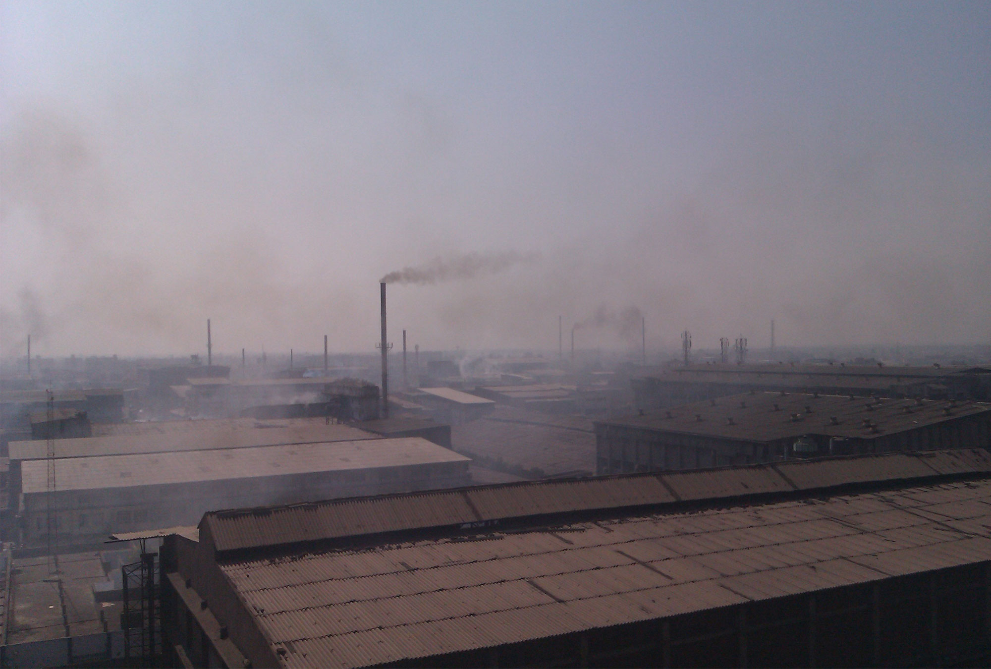 Smokestacks over roofs in India
