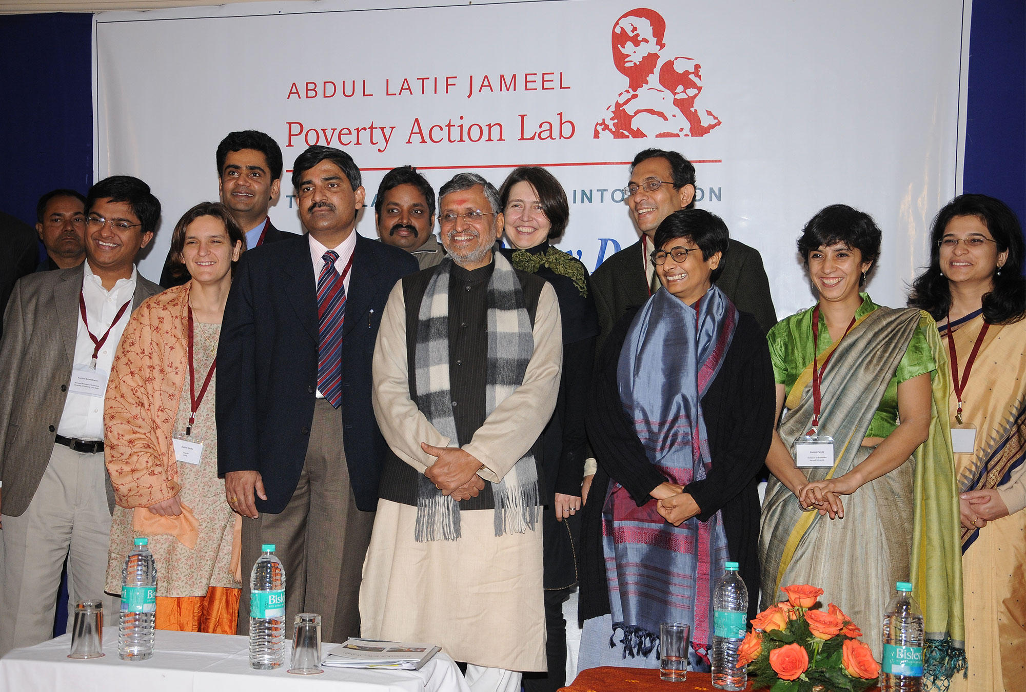 Group of J-PAL affiliates and partners stand in front of J-PAL logo banner