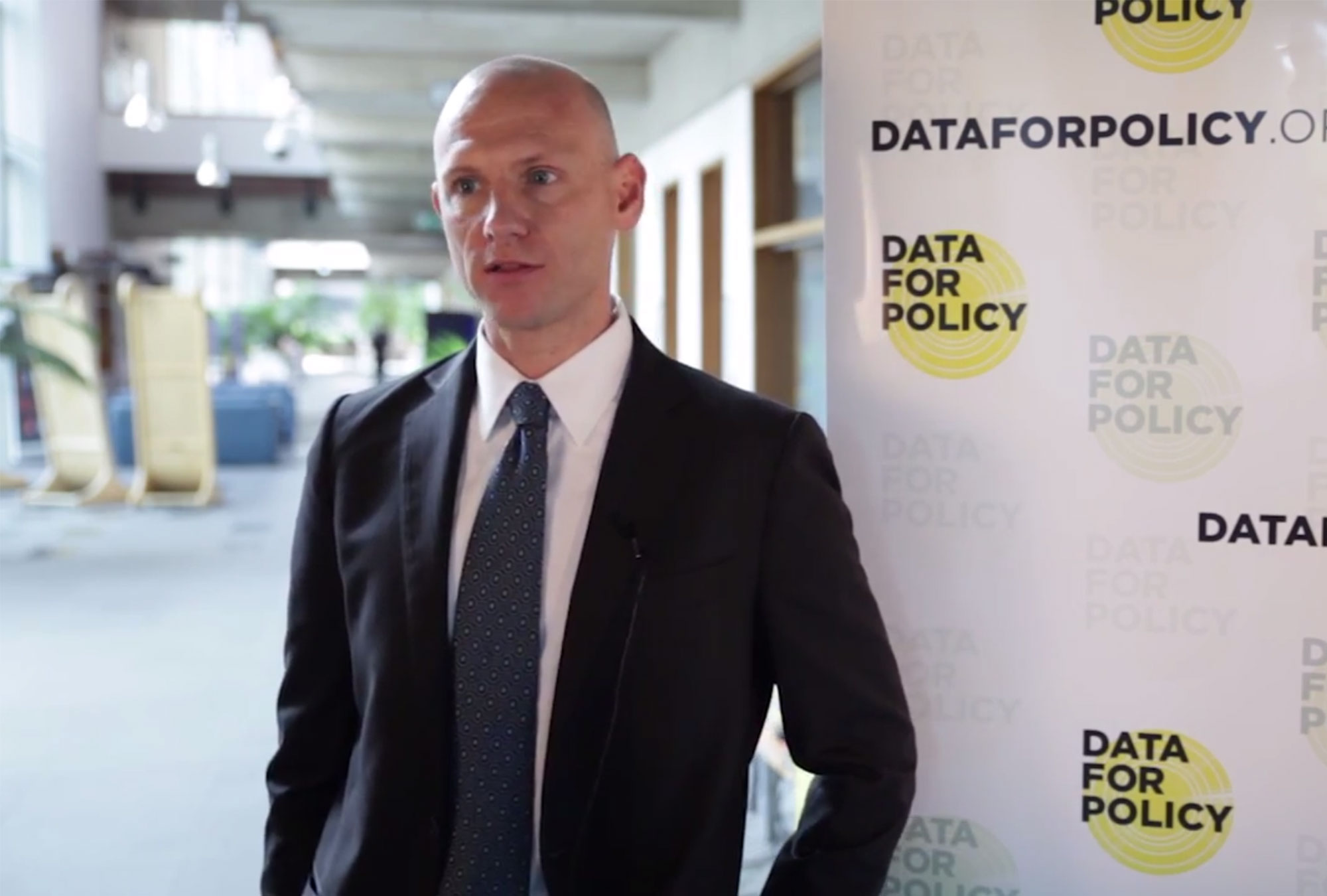 Quentin Palfrey stands in front of Data for Policy banner
