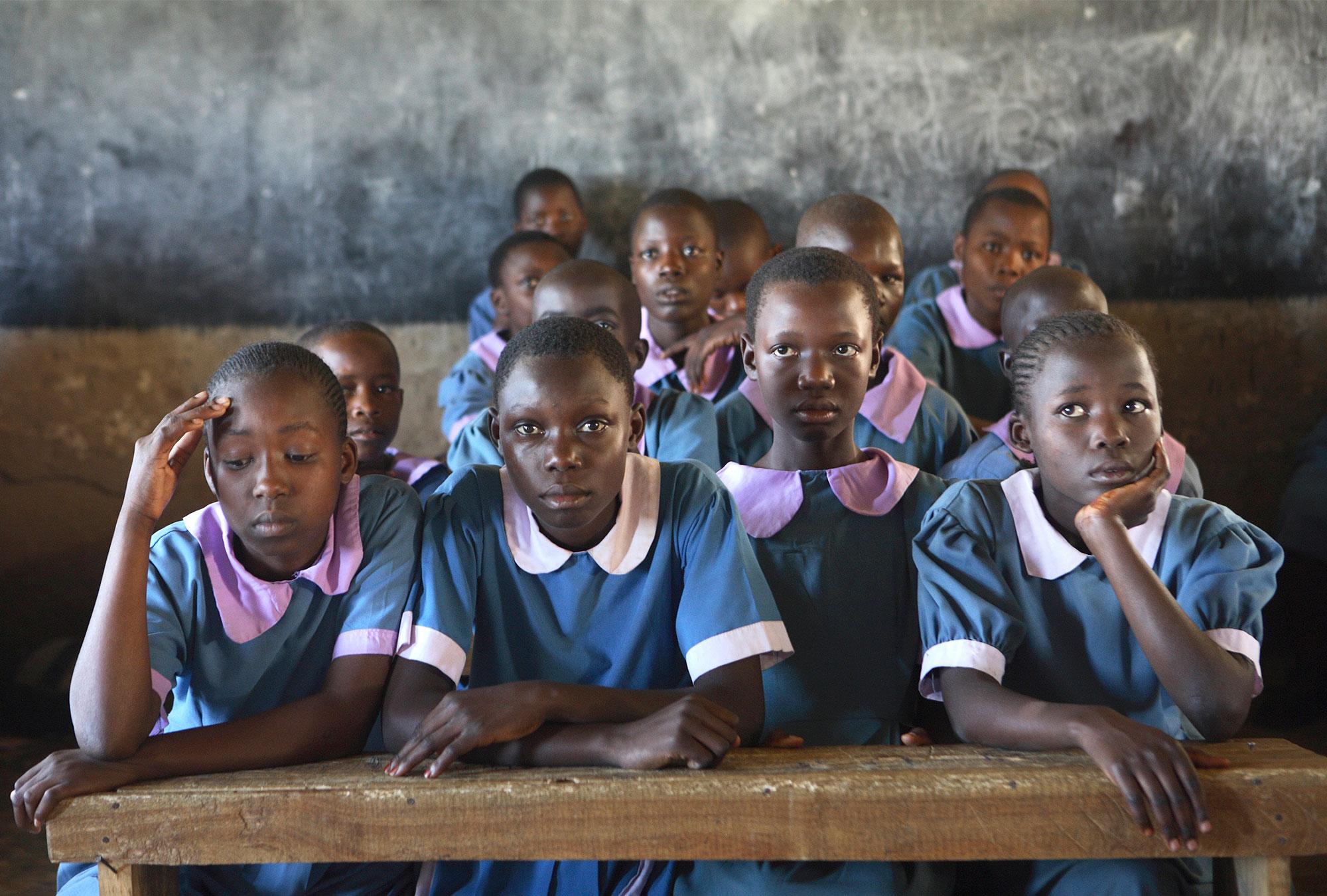 Girls in school uniforms sit in class
