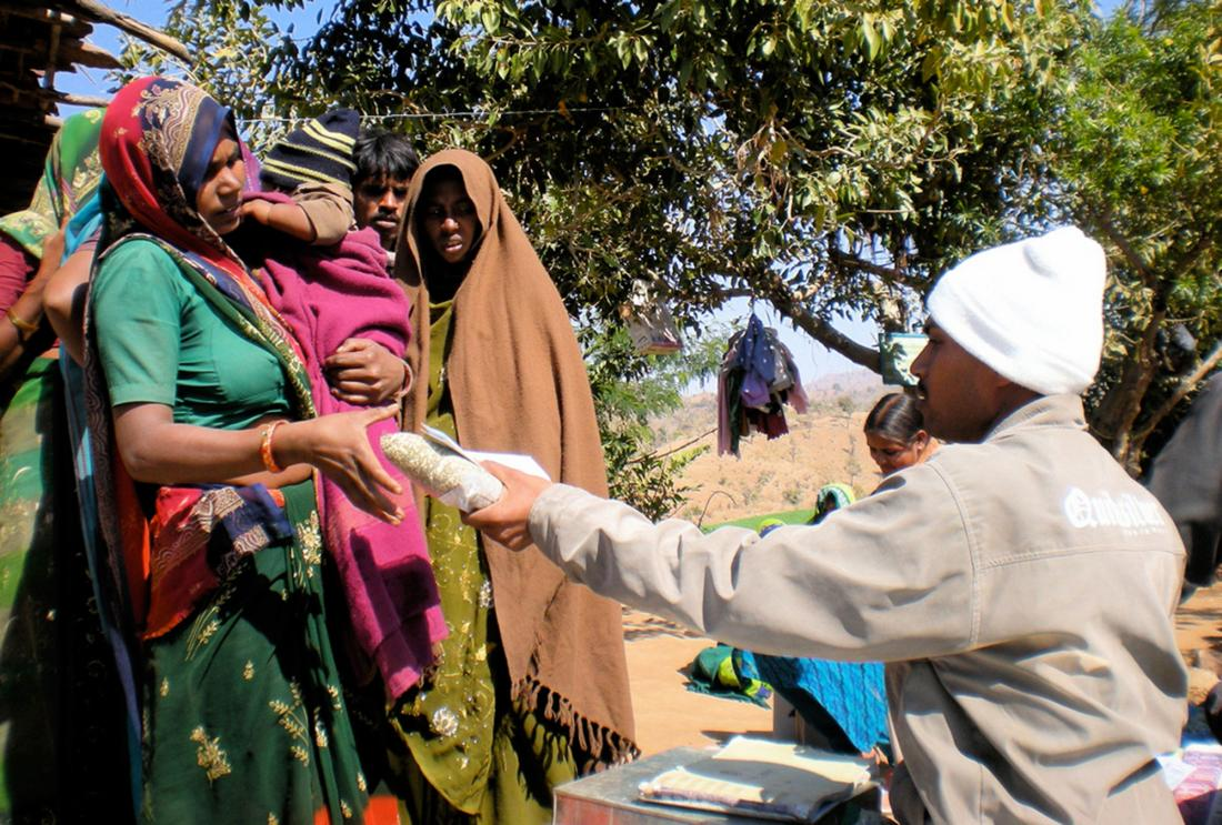 A parent receives a kilogram of lentils at a vaccination clinic in Rajasthan, India.
