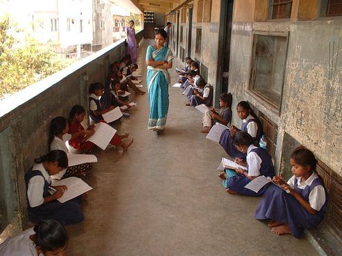 Uniformed students sit on school porch as teacher in sari watches