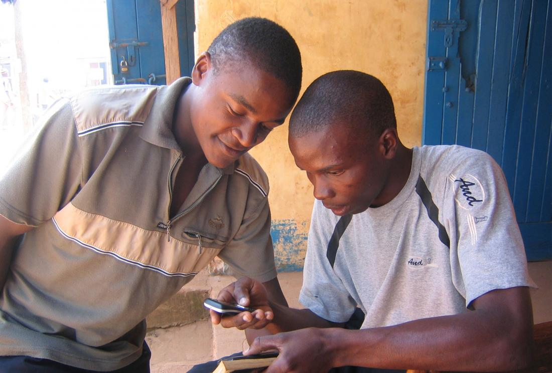 Two men look at mobile phone