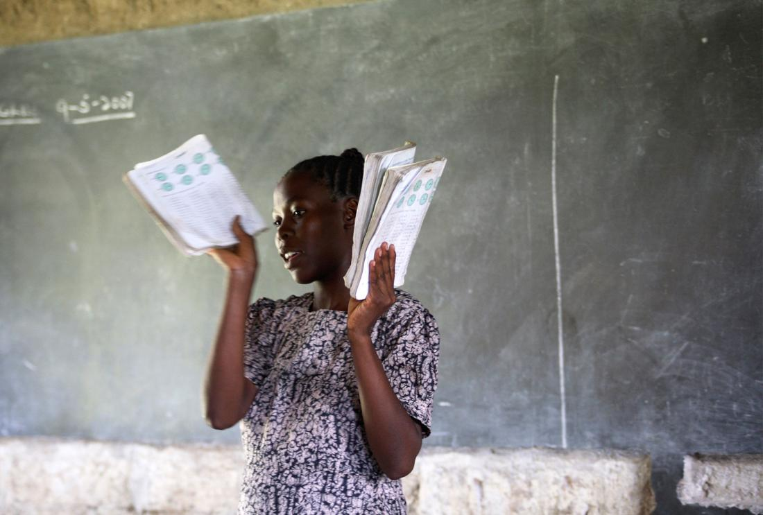 A teacher hands out textbooks to students in Kenya.