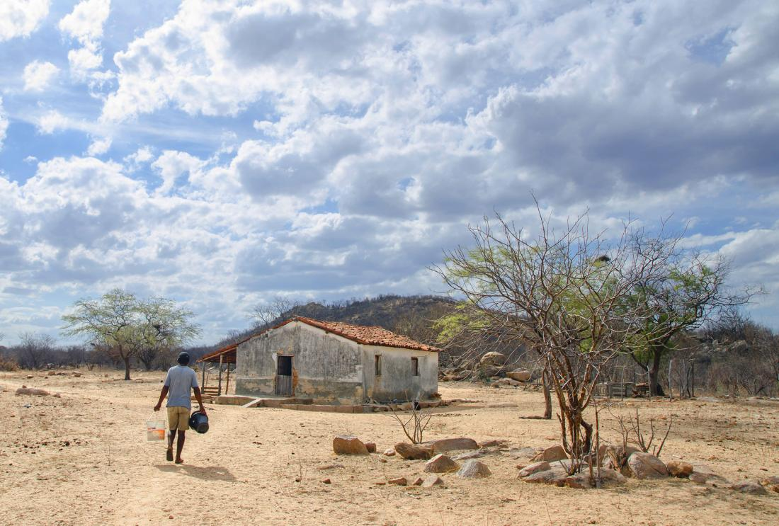 Man carries buckets of water to house in dry landscape