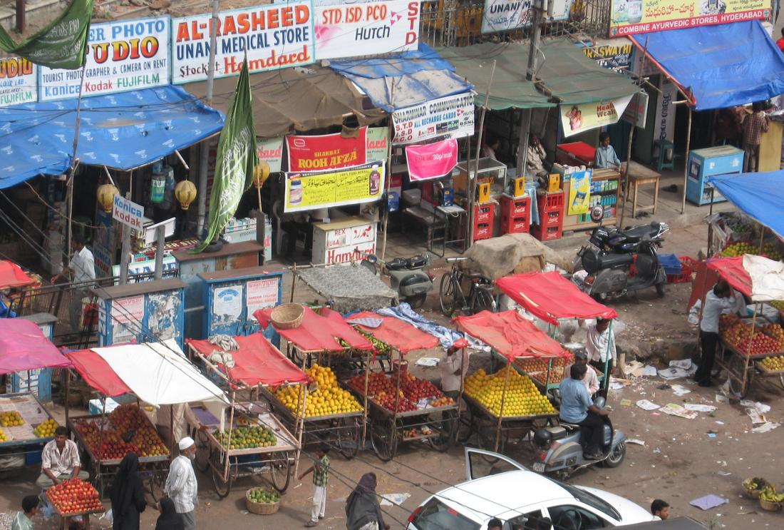 Street scene with fruit vendors and electronics stalls in Hyderabad, India
