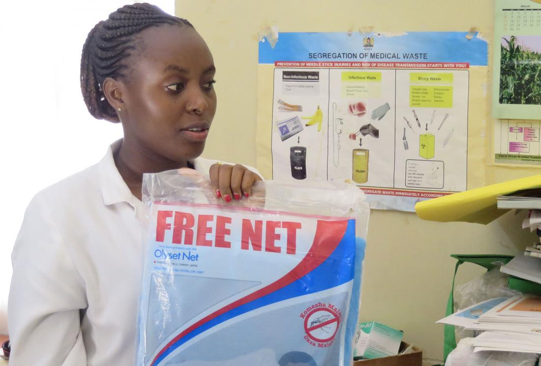 "Woman in lab coat holds package reading ""free bednet"""