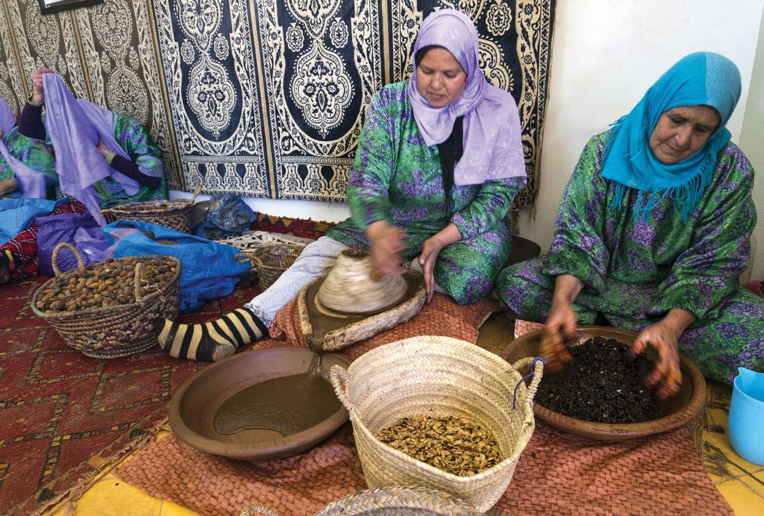 Women in headscarves seated on moroccan rugs process seeds