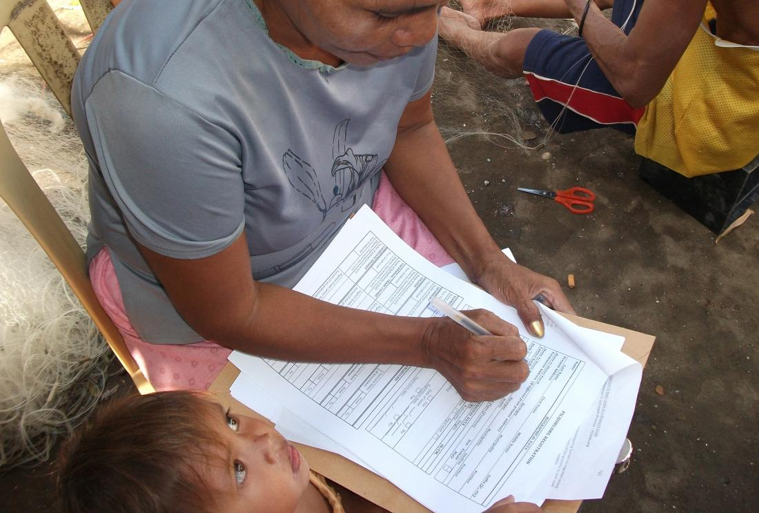 Woman fills out paper work in Philippines