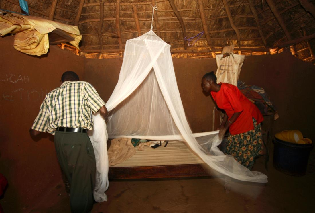 Man and woman assembling a bed net in rural Kenya.