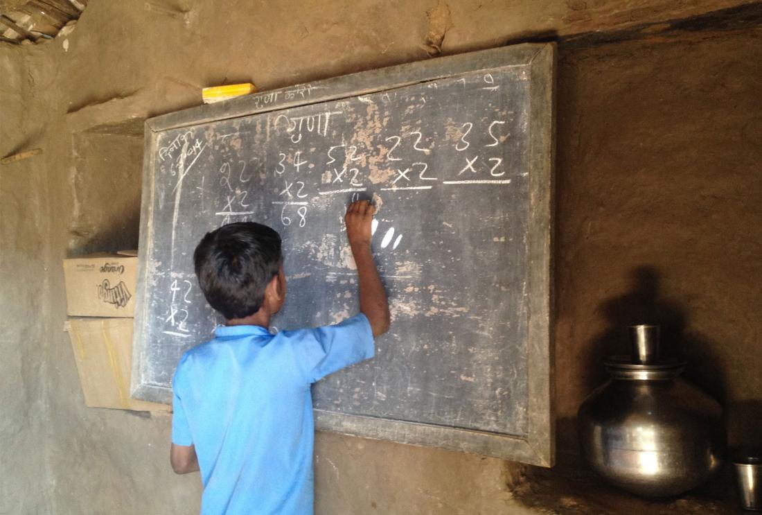 Boy writes sums on chalkboard
