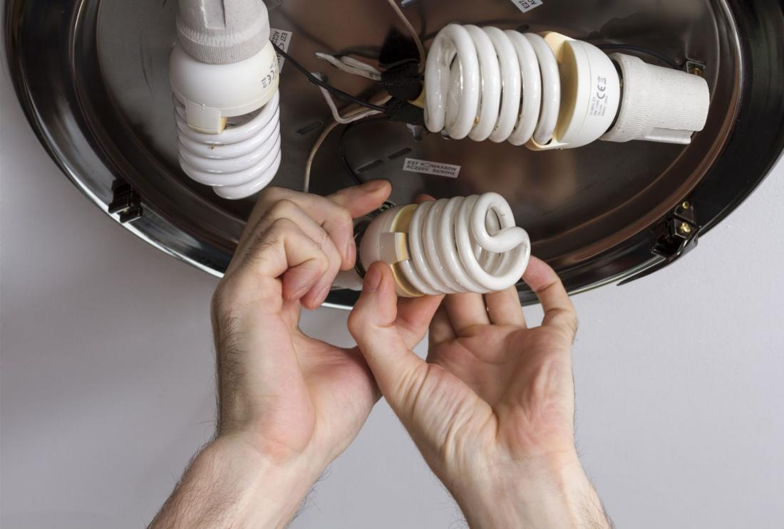 Electrician installing energy efficient lightbulbs