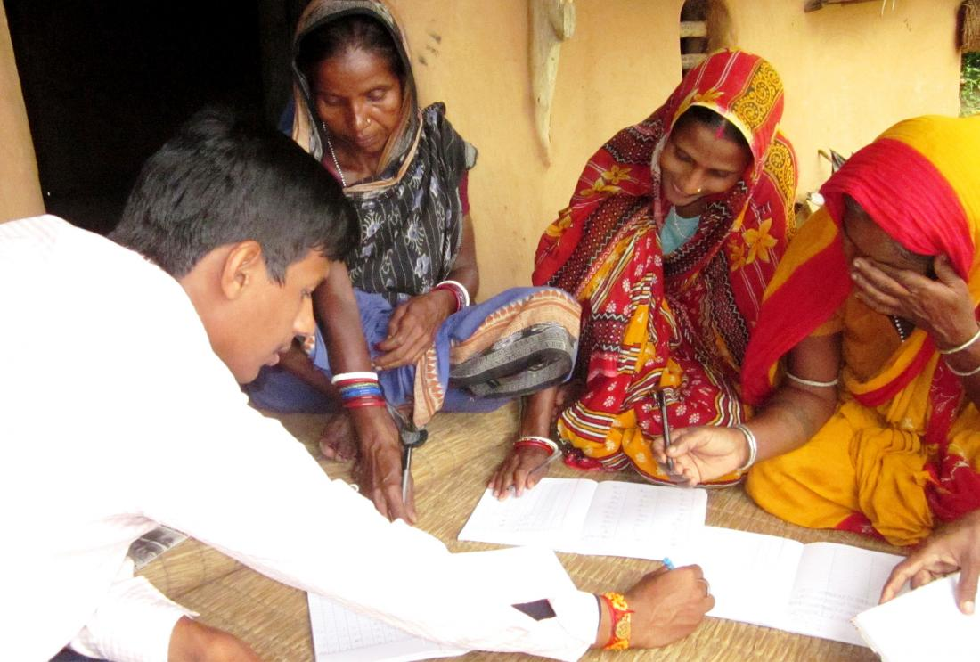 Three women in saris look at paperwork with Bandhan staff