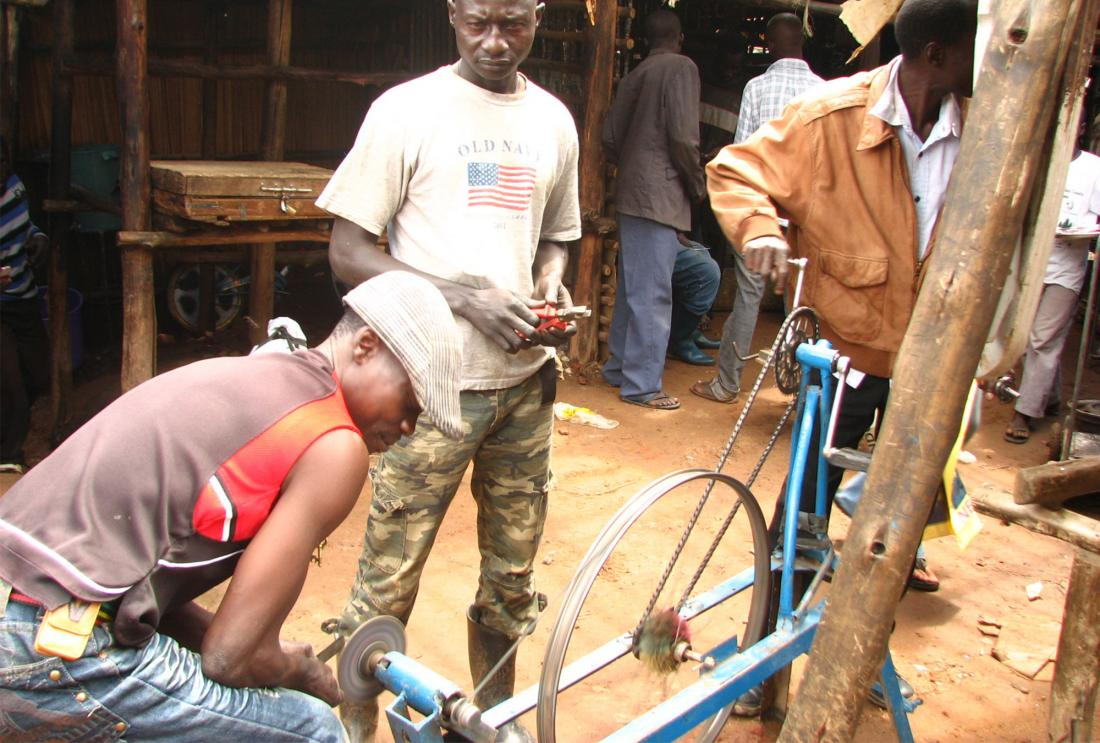 Men work on a bicycle in an open market