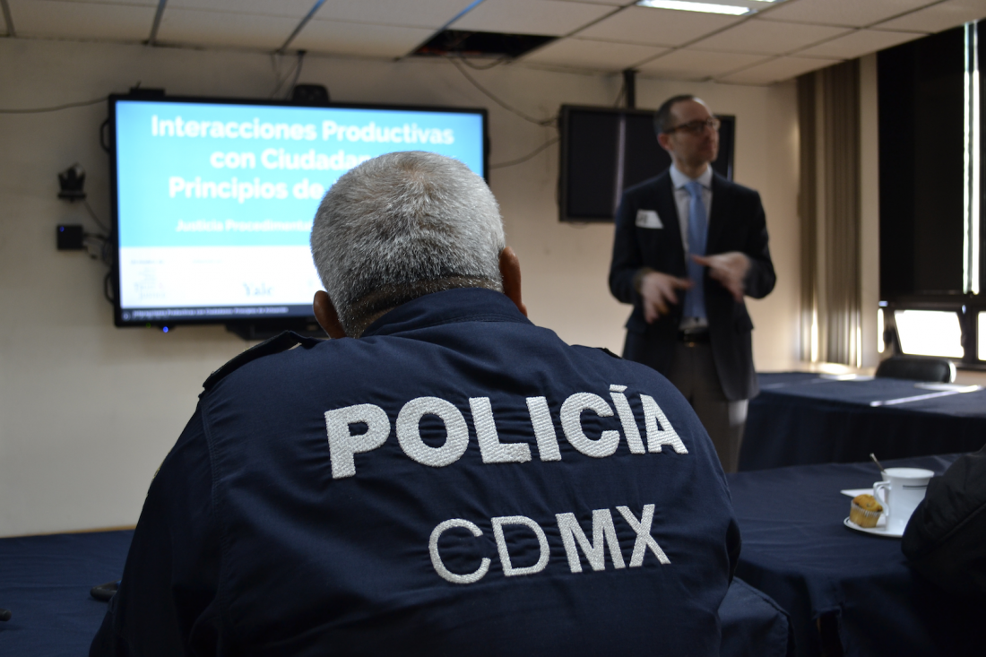 Man in suit gives presentation to policeman in Mexico City