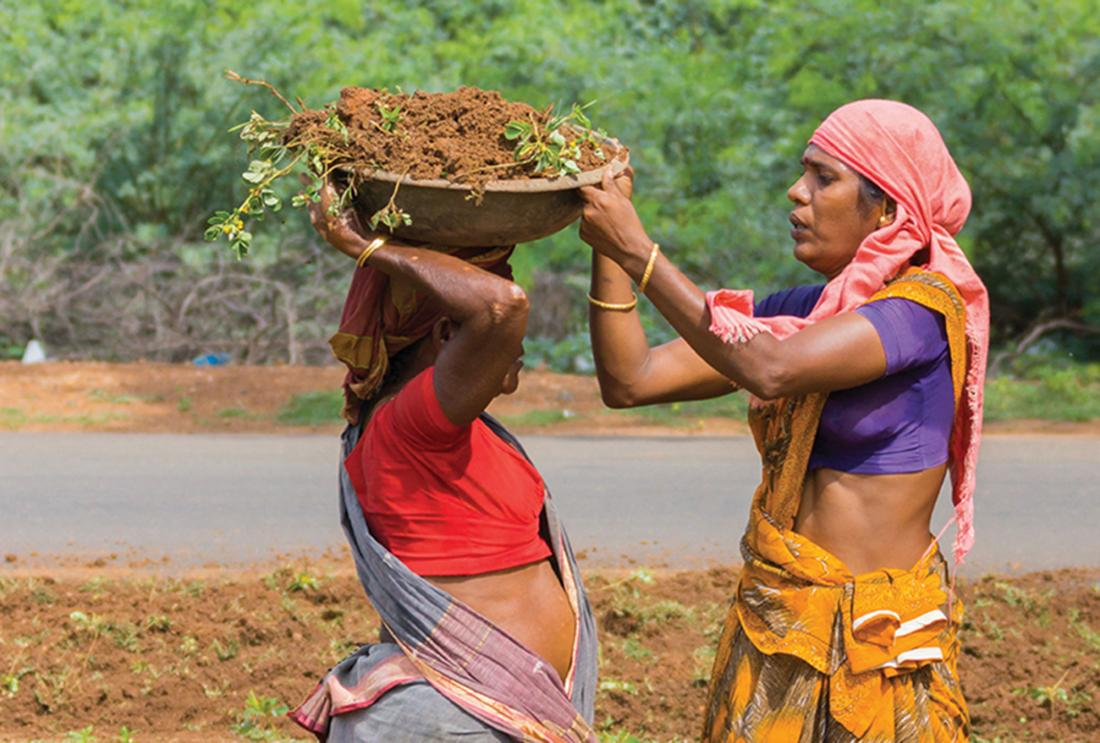 Women in India moving receptacles of dirt.