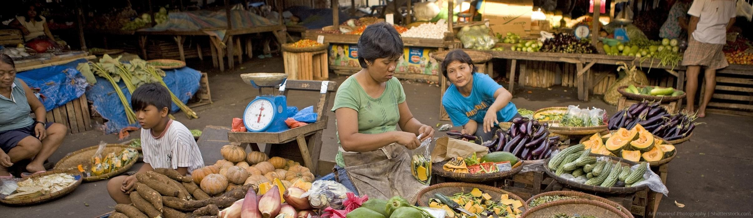 people at market selling fresh produce