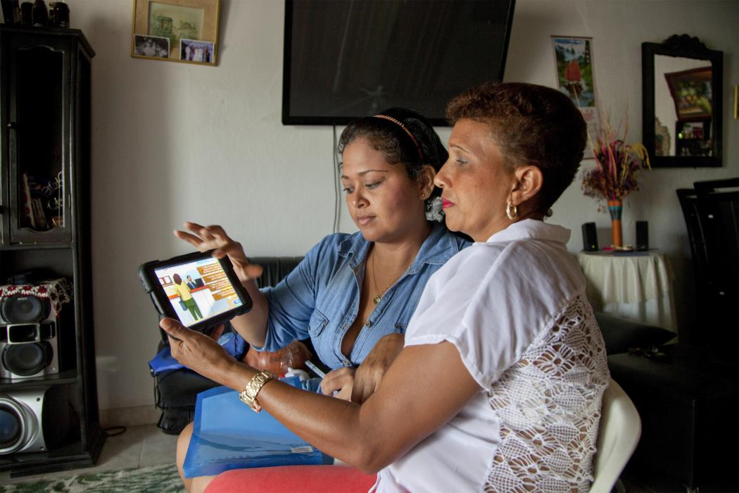 two women look at a tablet