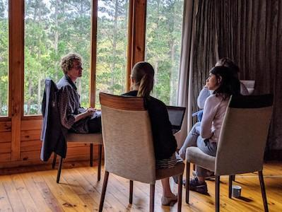 A researcher conducts an interview with three participants in a close circle