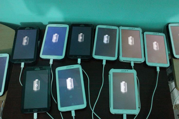 Many tablets lay charging on a table