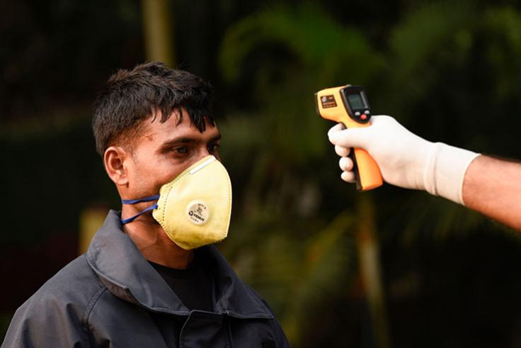 Temperature gun tests a man wearing a mask for COVID-19 in India