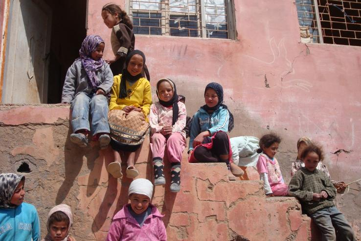Group of children in headscarves wait on stairs outside Moroccan school