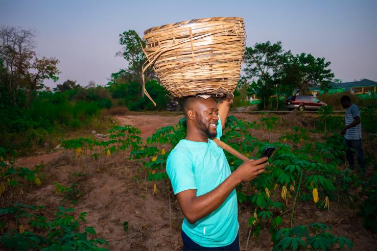 farmer holding a basket on his head and a cell phone in his hand