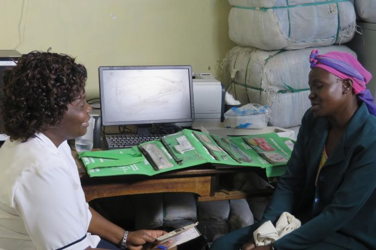 Zambian woman talks to nurse in front of table with birth control options