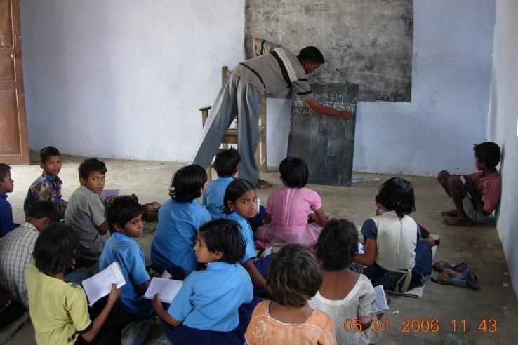 Indian children sitting on the floor of a classroom