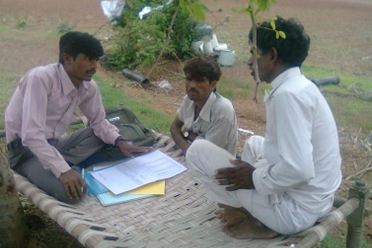 Three men talking over paperwork outdoors