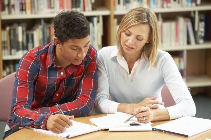 Woman and young man look at homework in a library