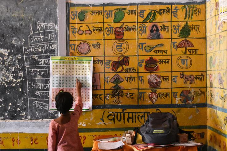 A child learning at a chart on the wall in a classroom.