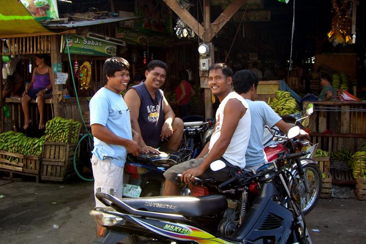 Smiling men in a market in the Philippines