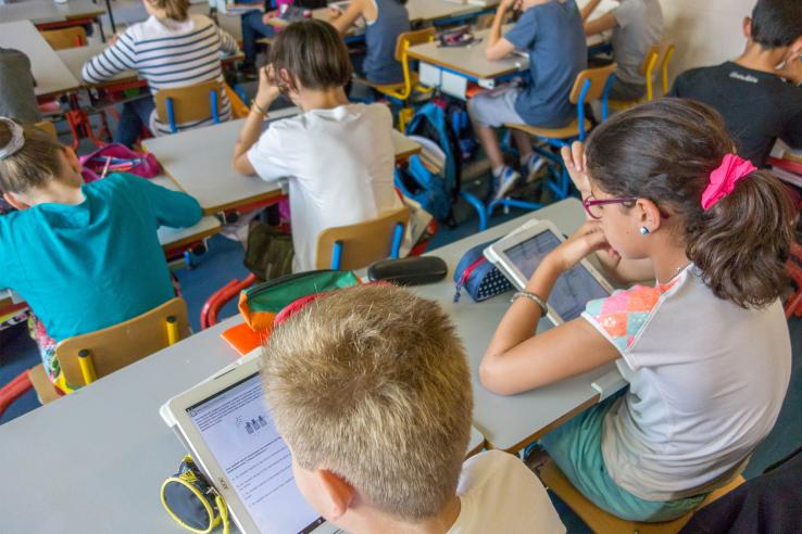 Children sit at desks looking at tablets