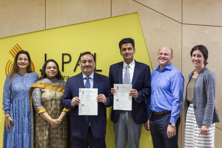 a group of people posing for the camera holding a certificate