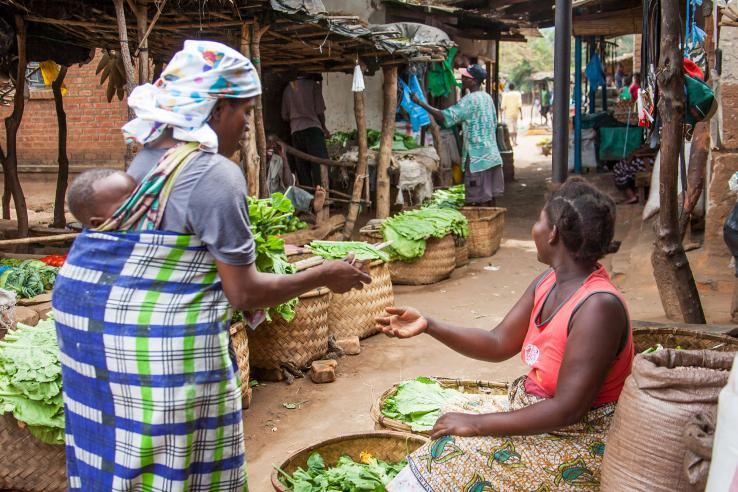 Woman carrying baby on her back pays for her greens at a rural market in Malawi