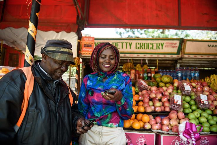 A man and a woman at a market looking at mobile phones