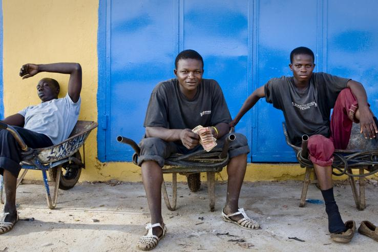 young men sitting in wheelbarrows