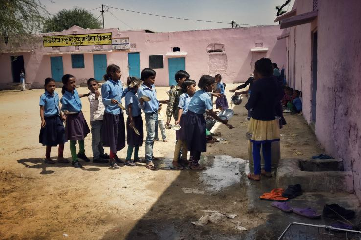 students in India line up to wash their dishes