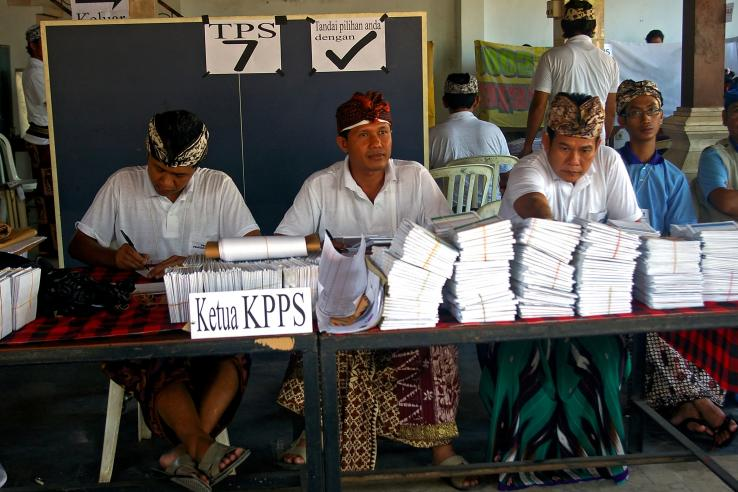 election officials with ballot papers in a polling station