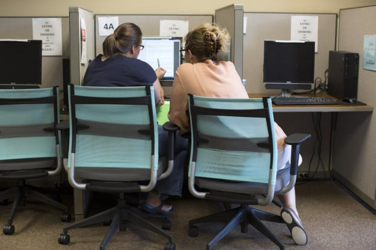 Two women sit before a computer screen.