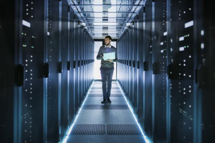 Man holding laptop walking through data center room