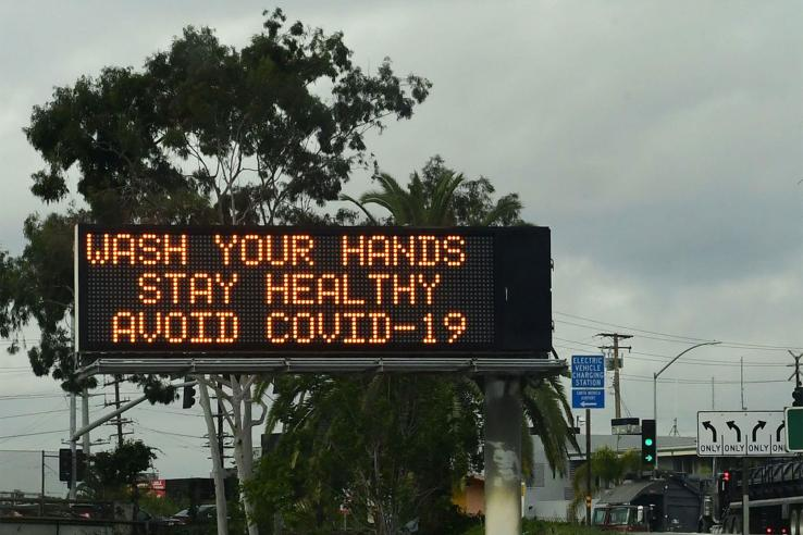 "A billboard along a highway reads ""Wash Your Hands. Stay Healthy. Avoid COVID-19."""