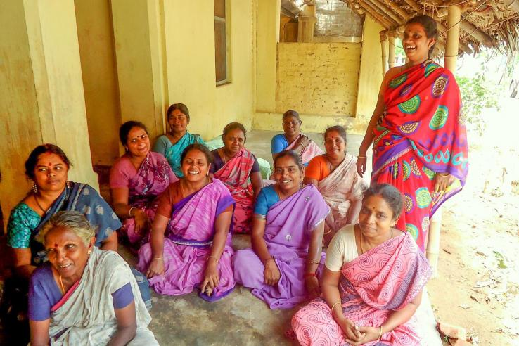 Women in India sitting on the floor for a focus group discussion.