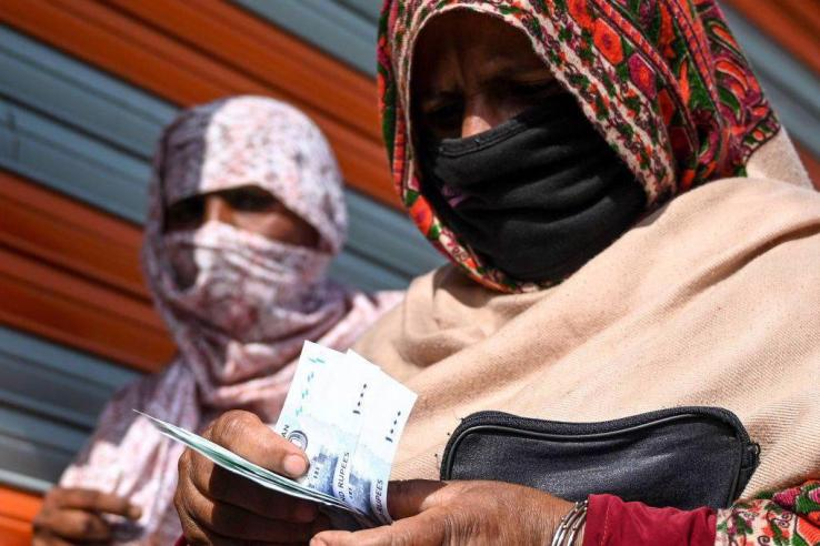 A woman wearing a medical face mask counts rupee notes after collecting cash of financial assistance through a mobile wallet under the governmental Ehsaas Emergency Cash Programme for families in need during a government-imposed nationwide lockdown as a preventive measure against the COVID-19 coronavirus, in Islamabad on April 9, 2020.