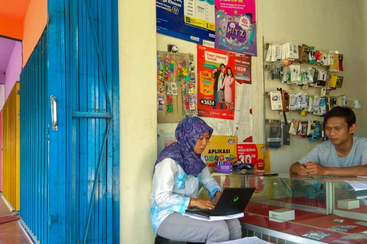 A man stands behind a counter that displays phone cards in a small shop. A woman sits in front of the counter typing on a laptop.
