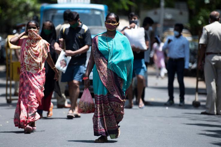 Women walk down a street wearing face masks
